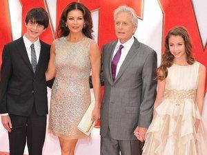 Michael Douglas stoi w szarym garniturze w szeregu wraz z żoną Catherine Zeta Jones w brokatowej krótkiej sukience i z dziećmi Dylanem w czarnym garniturze i Carys w kremowej sukience