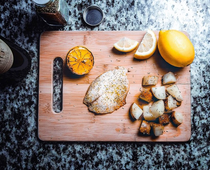 Pieczona ryba na desce z cytryną i ziemniakami