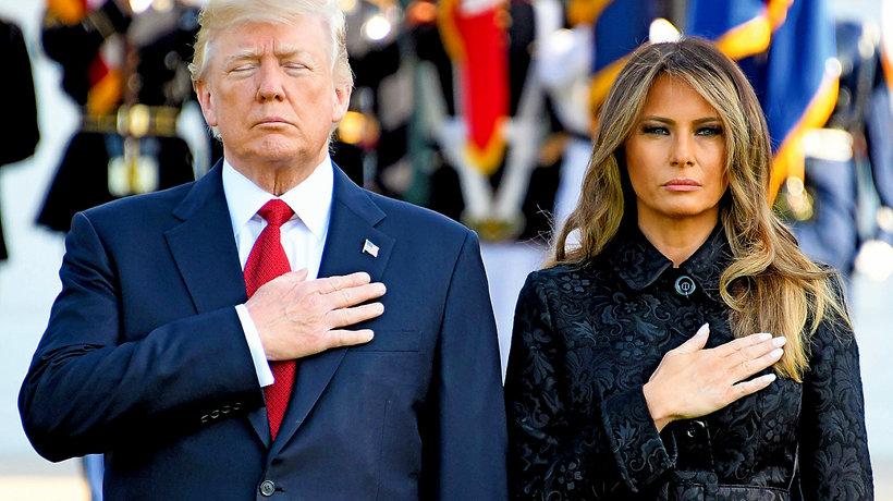 Donald i Melania Trump stoją obok siebie i trzymają ręce na piersiach