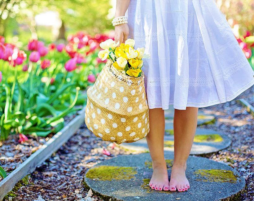 dziewczyna w ogrodzie z koszykiem i kwiatami