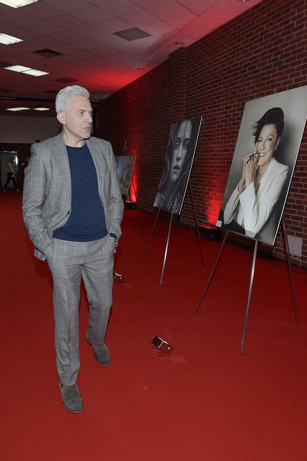Hubert Urbański w szarym garniturze ogląda zdjęcia