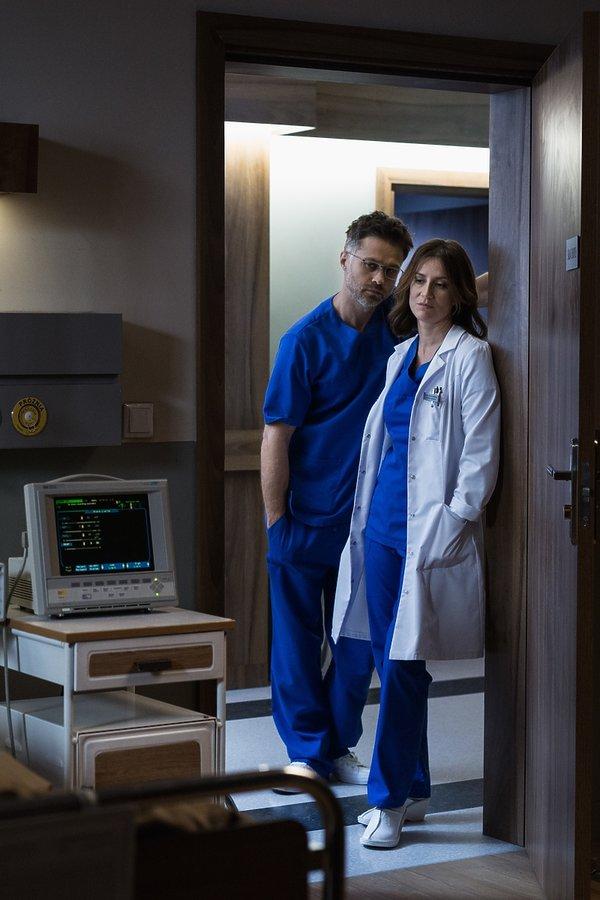Maja Ostaszewska i Maciej Zakościelny w lekarskich kitlach stoją oparci o drzwi do szpitalnej sali