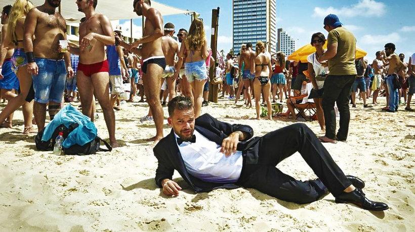 Michał Piróg w garniturze leży na plaży w Tel Awiwie