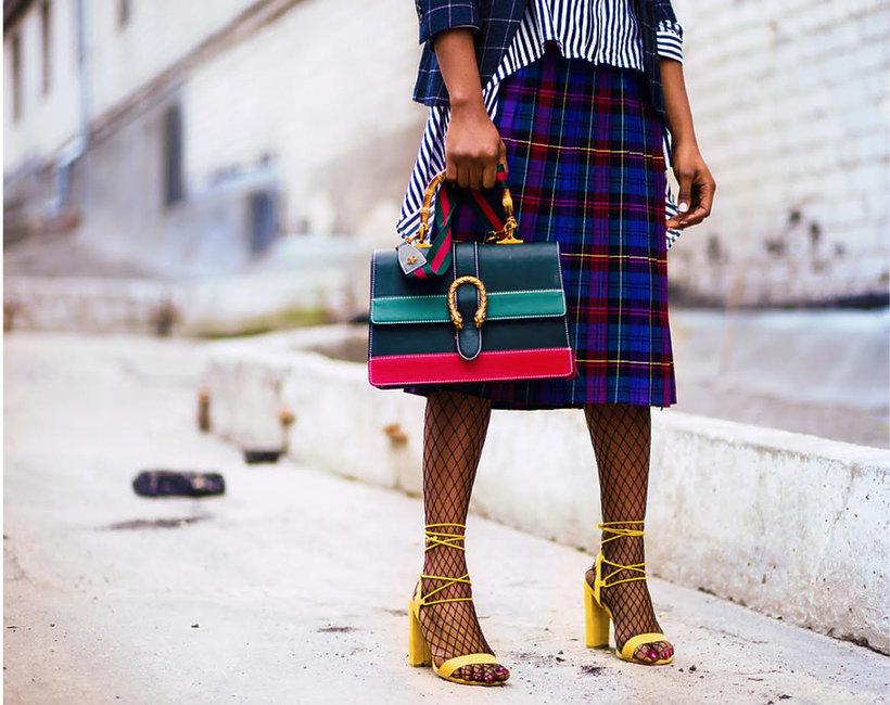nogi czarnoskórej kobiety w spódnicy z kolorową torebką