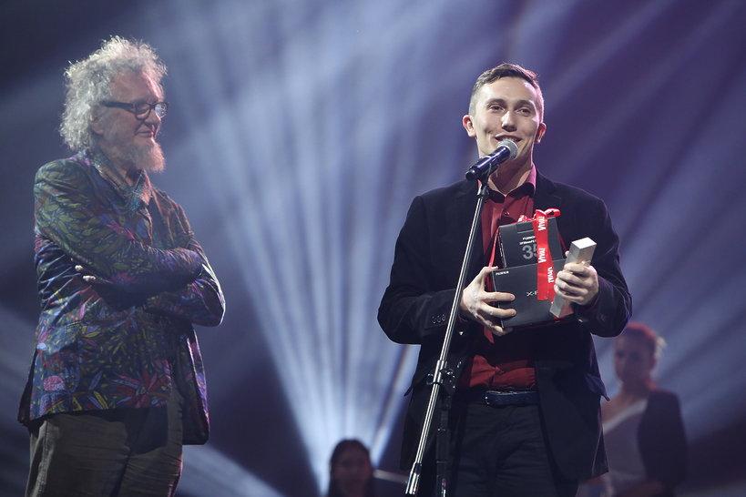 Tomasz Sikora wręcza nagrodę w kategorii reportaż