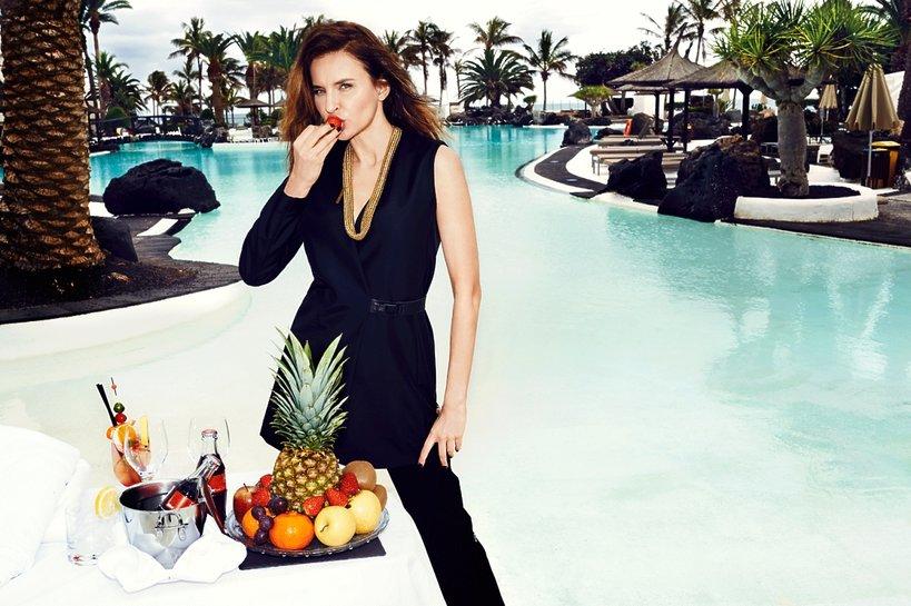 """Joanna Horodyńska w czarnej sukience je owoce  przy basenie, """"Viva!"""" marzec 2015"""