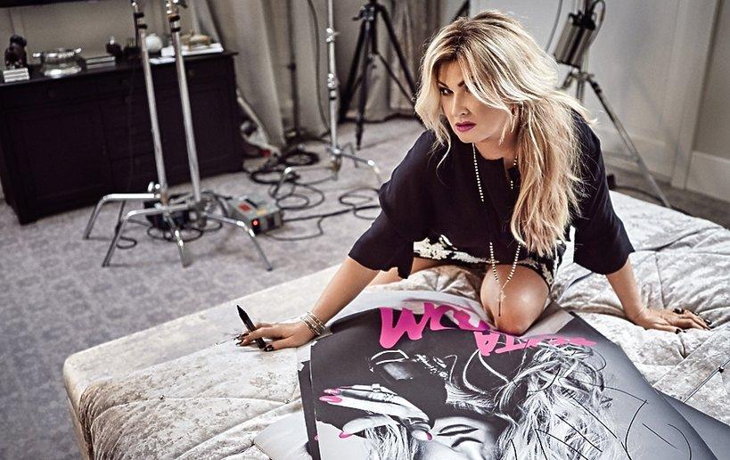Beata Kozidrak w czarnej bluzce i mini podpisuje się na plakacie
