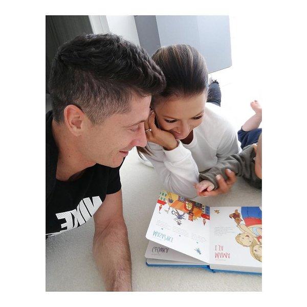 Anna Lewandowska i Robert Lewandowski czytają Klarze książkę