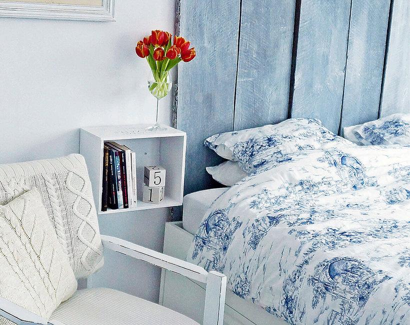 biało niebieska sypialnia  z czerwonymi kwiatami na szafce