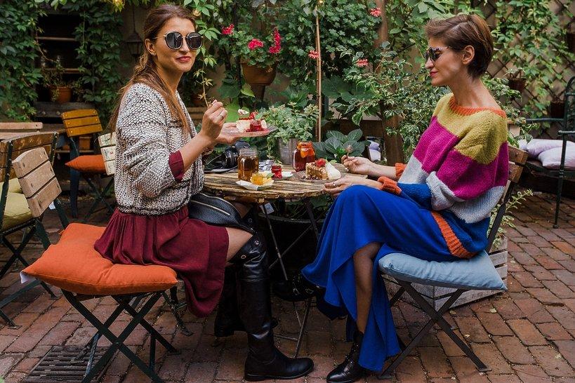 dwie kobiety siedzą przy stole w kawiarni