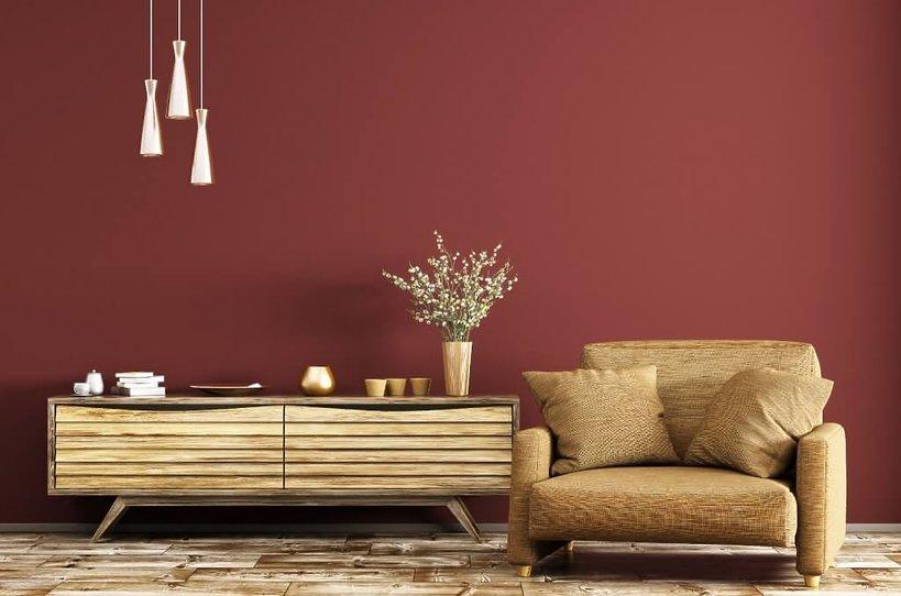 fotel i komoda w pokoju z czerwoną ścianą