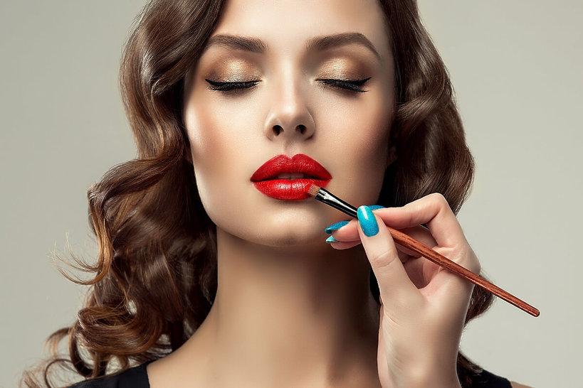 kobieta maluje pędzelkiem usta na czerwono