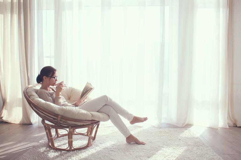 kobieta na krześle czyta książkę