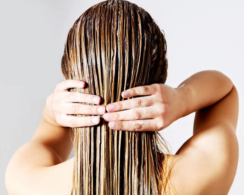 kobieta przeczesuje rękami mokre włosy