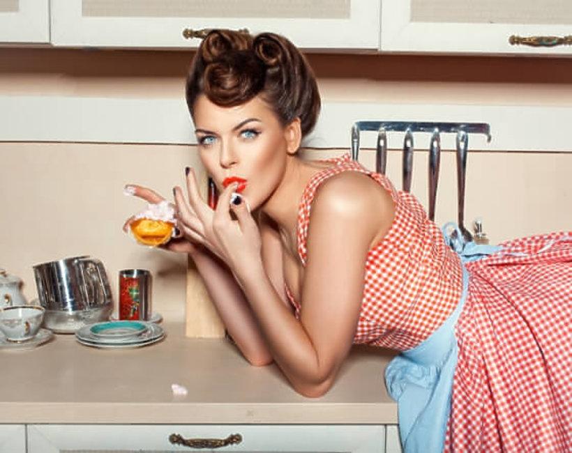 kobieta w stylu pin up je babeczkę w kuchni