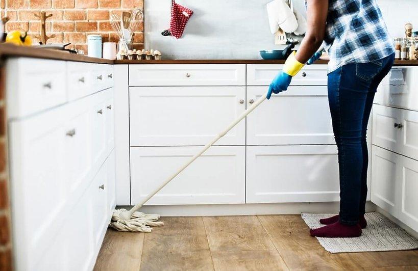 kobieta zamiata podłogę w kuchni