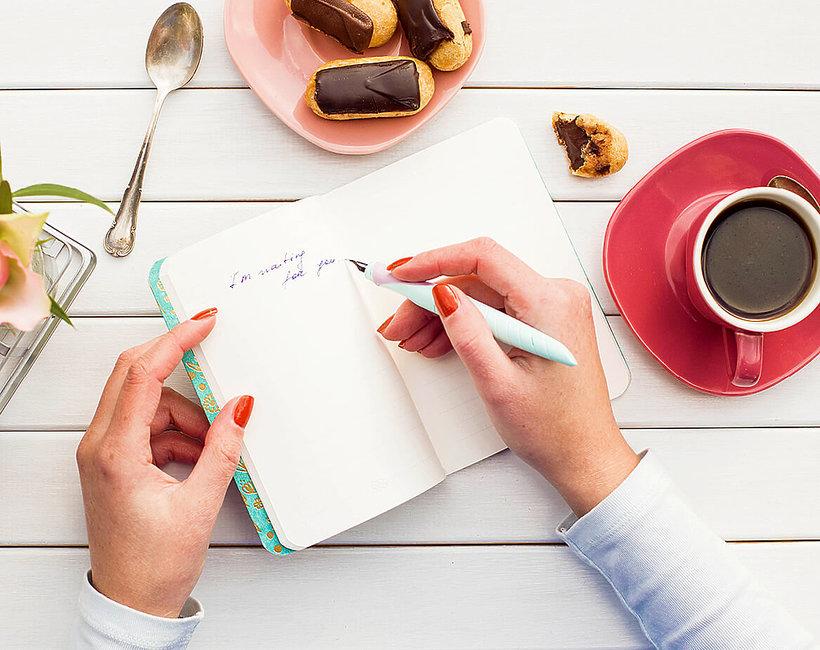 ręce notatnik ciasteczka i kawa