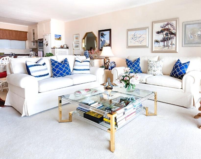 salon z białymi kanapami i niebieskimi dodatkami