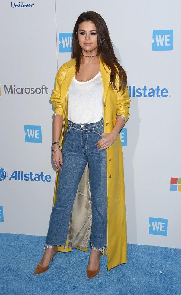 Modna stylizacja Seleny Gonez z przycietymi dżinsami i żółtym płaszczem