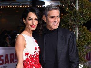 Amal Clooney w biało-czerwonej sukience i George Clooney w czarnym garniturze