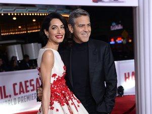 Amal Clooney w biało-czerwonej sukience i srebrnych szpilkach oraz George Clooney w czarnym garniturze