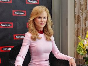 Nicole Kidman w różowej sukience siedzi na fotelu