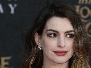 Anne Hathaway w pofalowanych włosach i z różową szminką