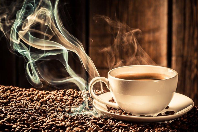 Filiżanka parującej kawy na ziarnach do zmielenia