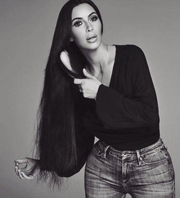 Kim Kardashian w jeansach i czarnej bluzce szczotkuje swje długie włosy