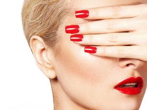 Kobieta w czerwonej szmince i z czerwonymi paznokciami zasłaniająca twarz dłonią