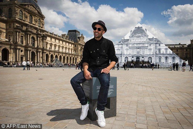 Artysta JR na tle muzeum w Luwrze